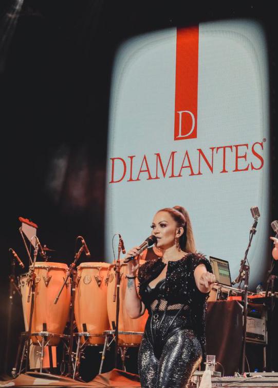 """Cantora Solange Almeida no palco da sua Live """"Minha História"""". A artista usa uma roupa preta e falando ao microfone. Ao fundo tem luzes do show e um painel grande de led com a loga da Diamantes Lingerie."""