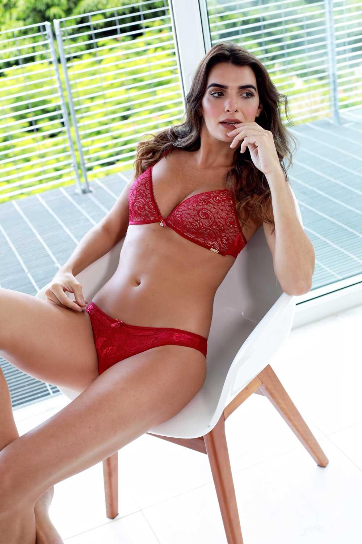 Modelo deitada usando uma lingerie vermelha com renda de design exclusivo.