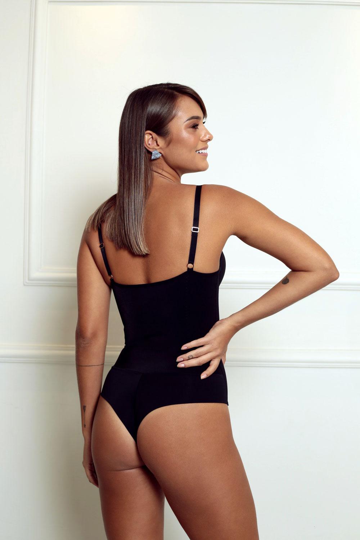 Modelo usando body modelador preto com calcinha fio.