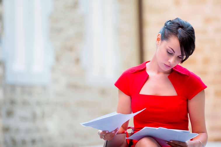 Mulher usando vestido vermelho sentada em lugar ao ar livre analisando papéis e documentos.