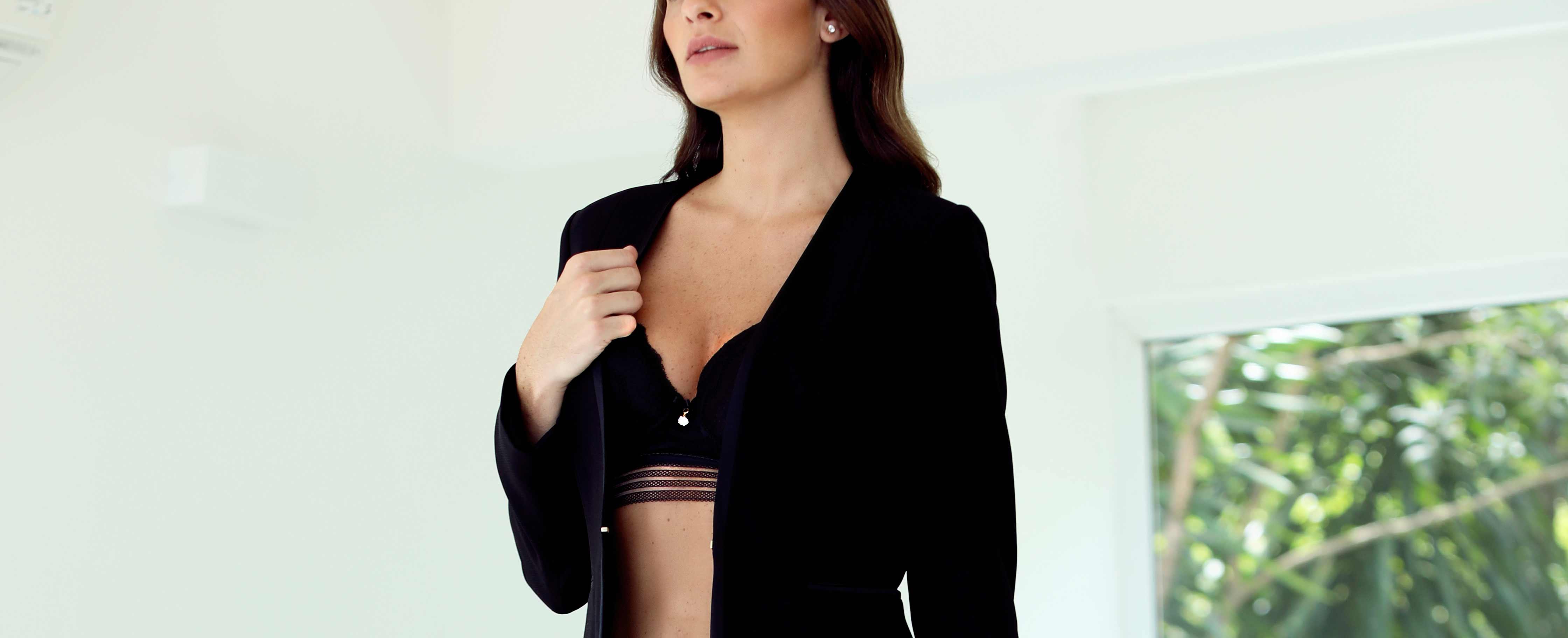 Modelo vestindo blazer preto e sutiã preto.