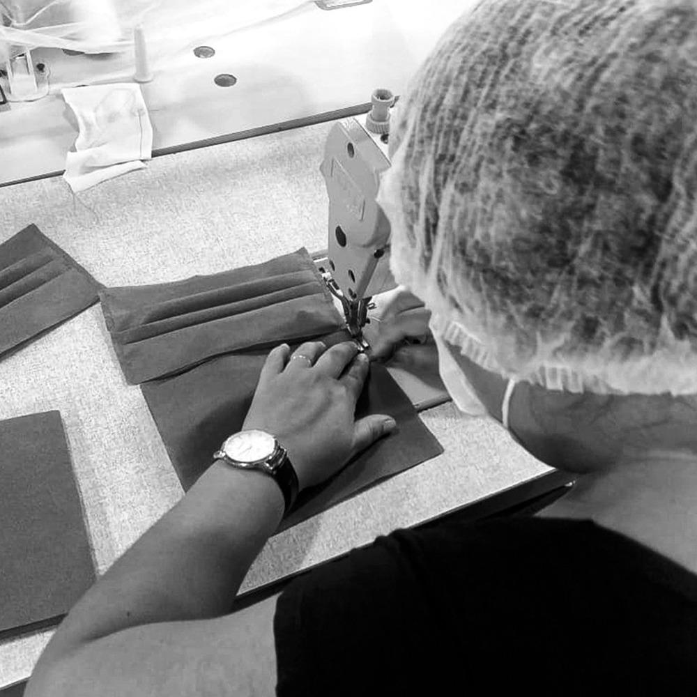 Costureira da Diamantes Lingerie usando touca e máscara fabricando máscara de proteção.