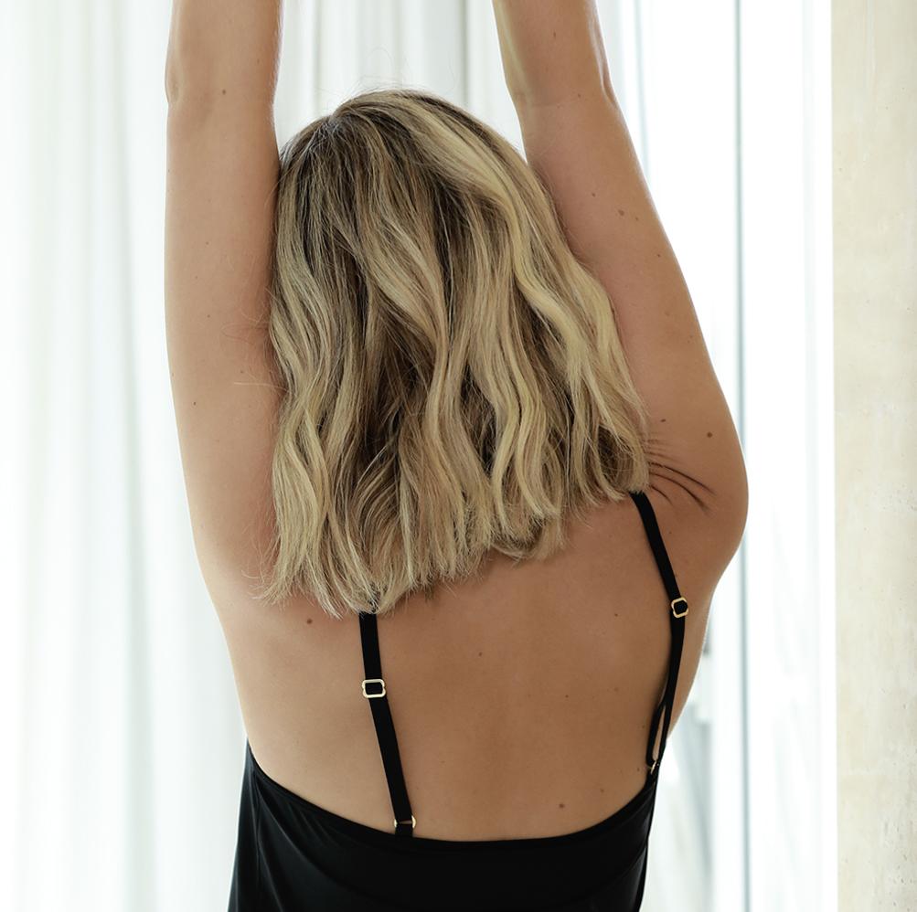 Mulher de costas com braços pra cima, sentindo o conforto de usar Diamantes.