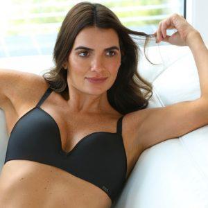 Modelo sentada no sofá vestindo sutiã preto essencial.