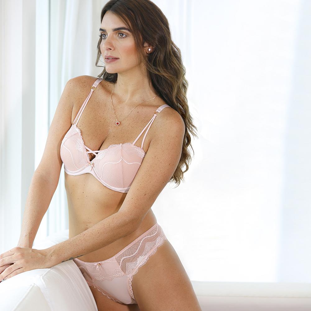 Modelo apoiada no sofá usando lingerie sofisticada na cor essência (rosa claro).