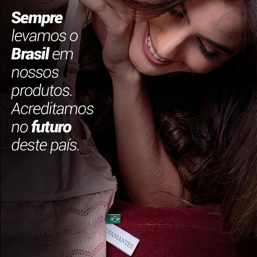 """Mulher segurando uma lingerie e olhando para a etiqueta personalizada com a bandeira do Brasil. Ao lado tem uma frase que diz: """"Sempre levamos o Brasil em nossos produtos. Acreditamos no futuro deste país""""."""