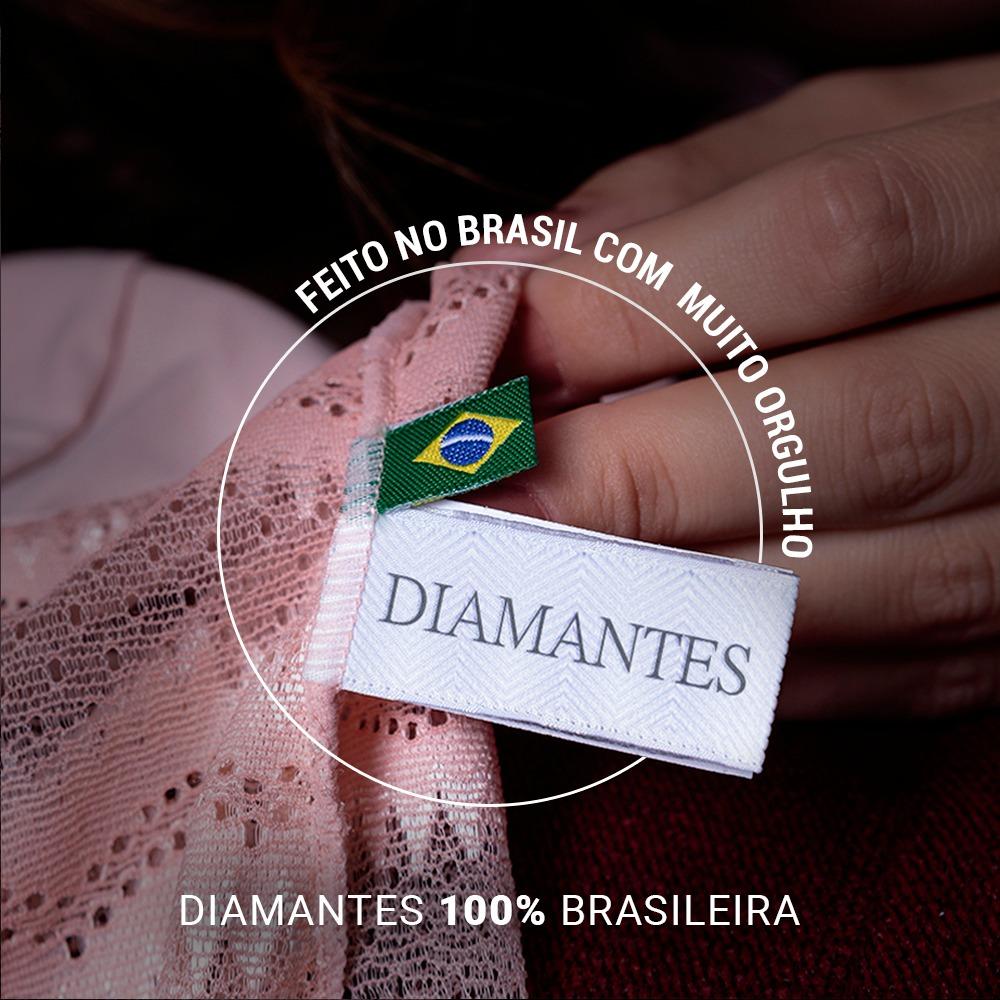 """Imagem de uma mão segurando um produto Diamantes destacando duas etiquetas: uma com a logo da Diamantes e outra personalizada com a bandeira do Brasil. As bandeiras estão dentro de círculo que diz: """"Feito no Brasil com muito orgulho"""". Na parte inferior central há uma frase: """"Diamantes 100% brasileira""""."""