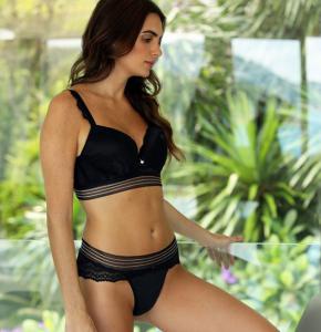 Modelo apoiada no vidro vestindo lingerie sofisticada preta com renda.