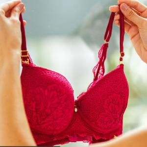Mãos femininas seguram um sutiã Diamantes na cor rosa pink com renda, pingente, bojo e aro.