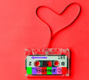 Fita cassete com um símbolo de coração isolado no fundo vermelho.