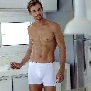 Modelo encostado numa bancada branca, usando uma cueca boxer da Diamantes na cor branca.