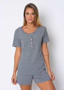 Modelo usando pijama, camisa com mangas e short mais soltinho, no tecido mescla - fundo cinza com corações pequenos na cor rosa e detalhes inspirados no crochê rosa.