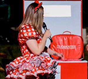 Solange Almeida em sua última live vestindo vestido de São João vermelho com bolinhas brancas no stand da Diamantes Lingerie.