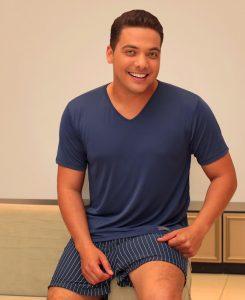 Imagem mostra o cantor Wesley Safadão sentado no sofá usando um homewear (camisa e calção) Diamantes na cor azul marinho. O calção é listrado com listras brancas. A camisa é totalmente lisa.