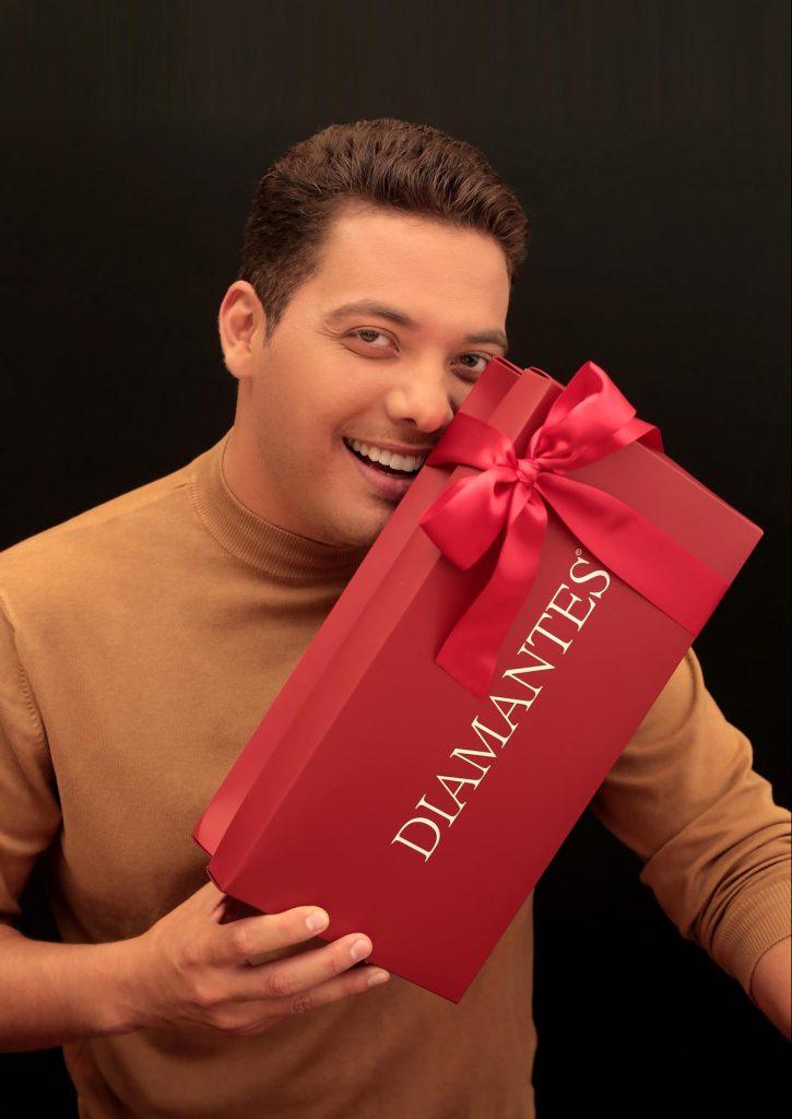 """O cantor Wesley Safadão, embaixador da marca, está num fundo preto, usa uma camisa marrom, e está segurando uma caixa de presente vermelha, com laço vermelho e na tampa tem """"Diamantes"""". Ele segura a caixa próximo ao rosto e sorri."""
