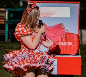 Solange Almeida em sua última live vestindo vestido de São João vermelho com bolinhas brancas segurando uma calcinha Diamantes Lingerie na cor rosa, com renda, fio e cintura alta.