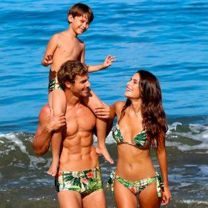 Foto de família na praia. Homem, mulher e menino nos ombros do homem. O homem usa sunga, menino usa sunga e mulher biquíni. Ambos vestem beachwear Diamantes com estampa exclusiva.