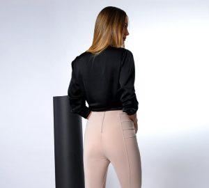 Modelo de costas vestindo calça rosa e blusa de manga preta. Por baixo modelo usa calcinha D-Skin Diamantes, zero marcas, que não marca na roupa.