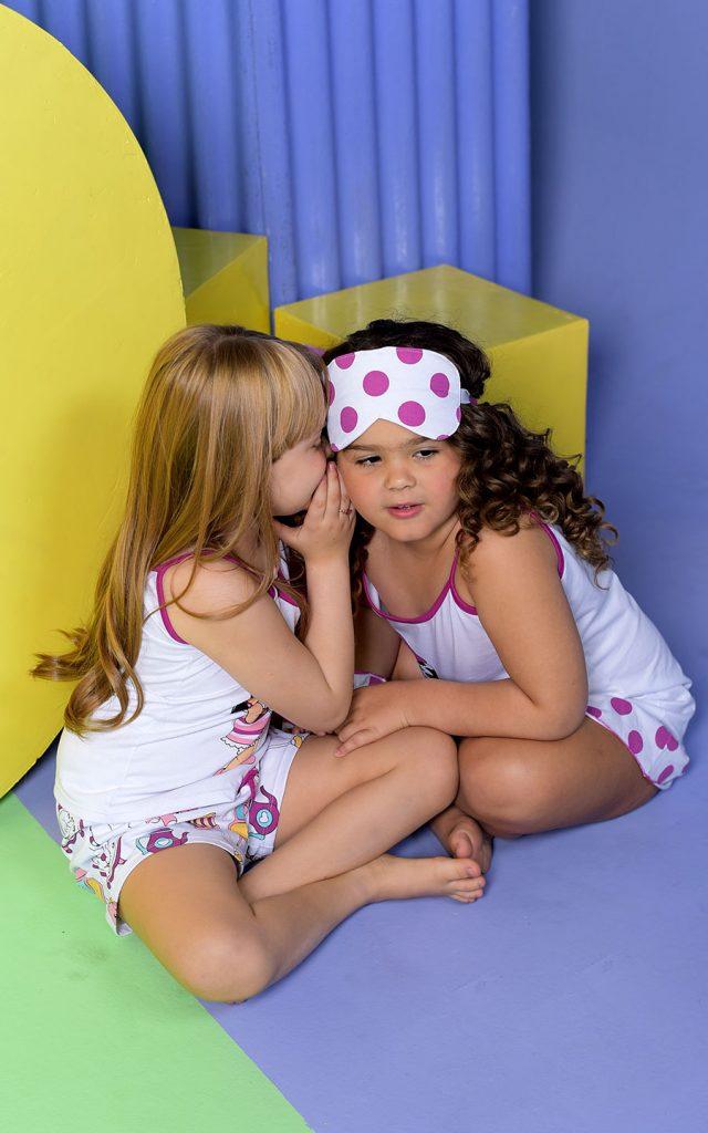 Duas meninas sentadas no chão contanto segredos uma para outra. A menina da esquerda usa short doll e a da direita usa camisola Diamantes.