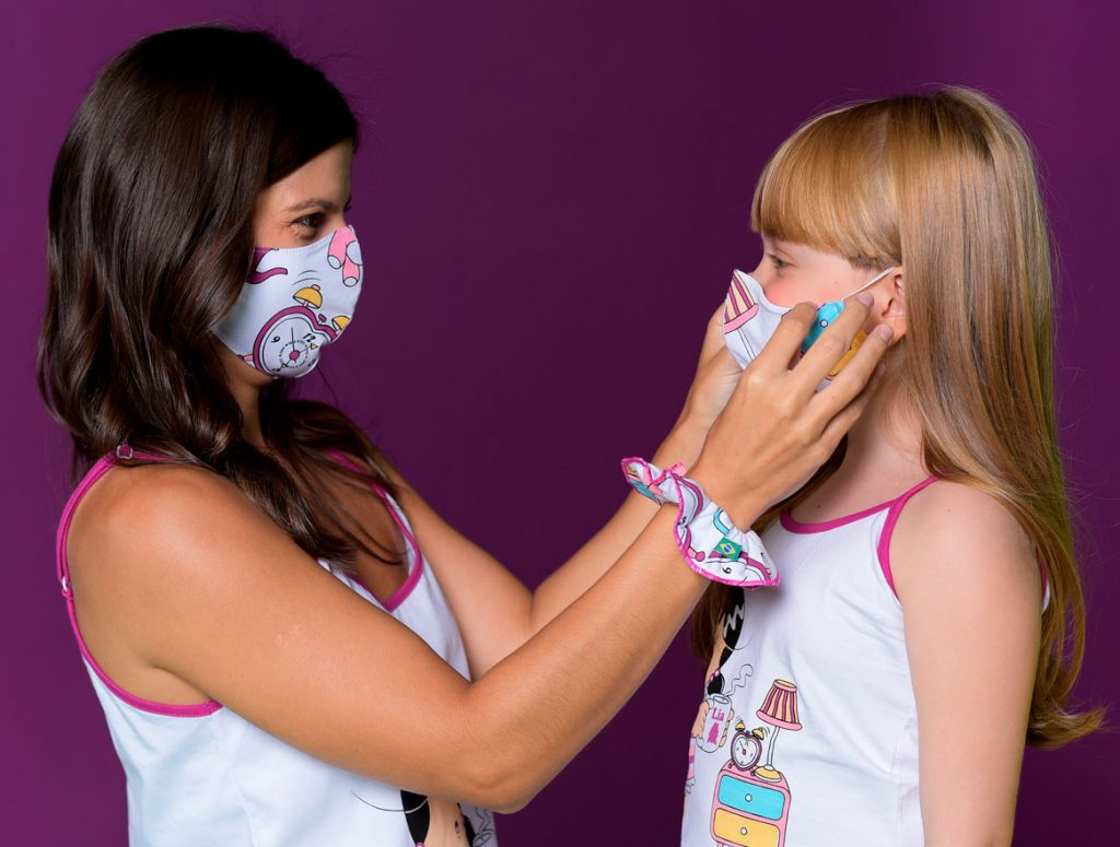 Modelos mãe e filha vestem pijamas Diamantes da Turma da Lia e usando máscara. A mãe está ajustado a máscara no rosto da filha. Ambas estão num fundo roxo.