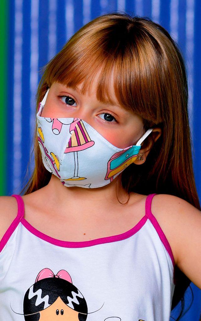 Modelo criança vestindo short doll da Turma da Lia e máscara de proteção com estampa exclusiva. Fundo verde, amarelo e azul.