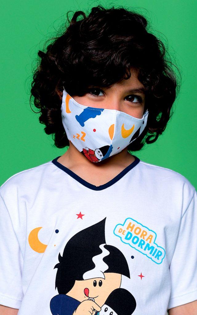 Modelo criança vestindo blusa da Turma do Aui e máscara de proteção com estampa exclusiva. Fundo verde.