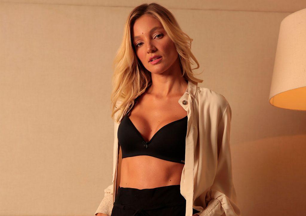 Modelo veste sutiã de Bojo High Tech na cor preta. A modelo está próxima a uma parede e olha para a câmera. Ela veste uma calça preta e blusa branca aberta na frente, expondo o sutiã.