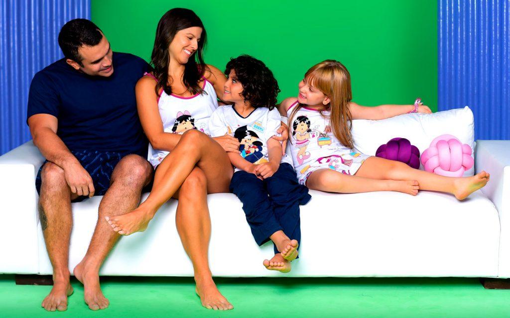 Família usando homewear Diamantes sentada num sofá branco. Fundo da imagem é verde.