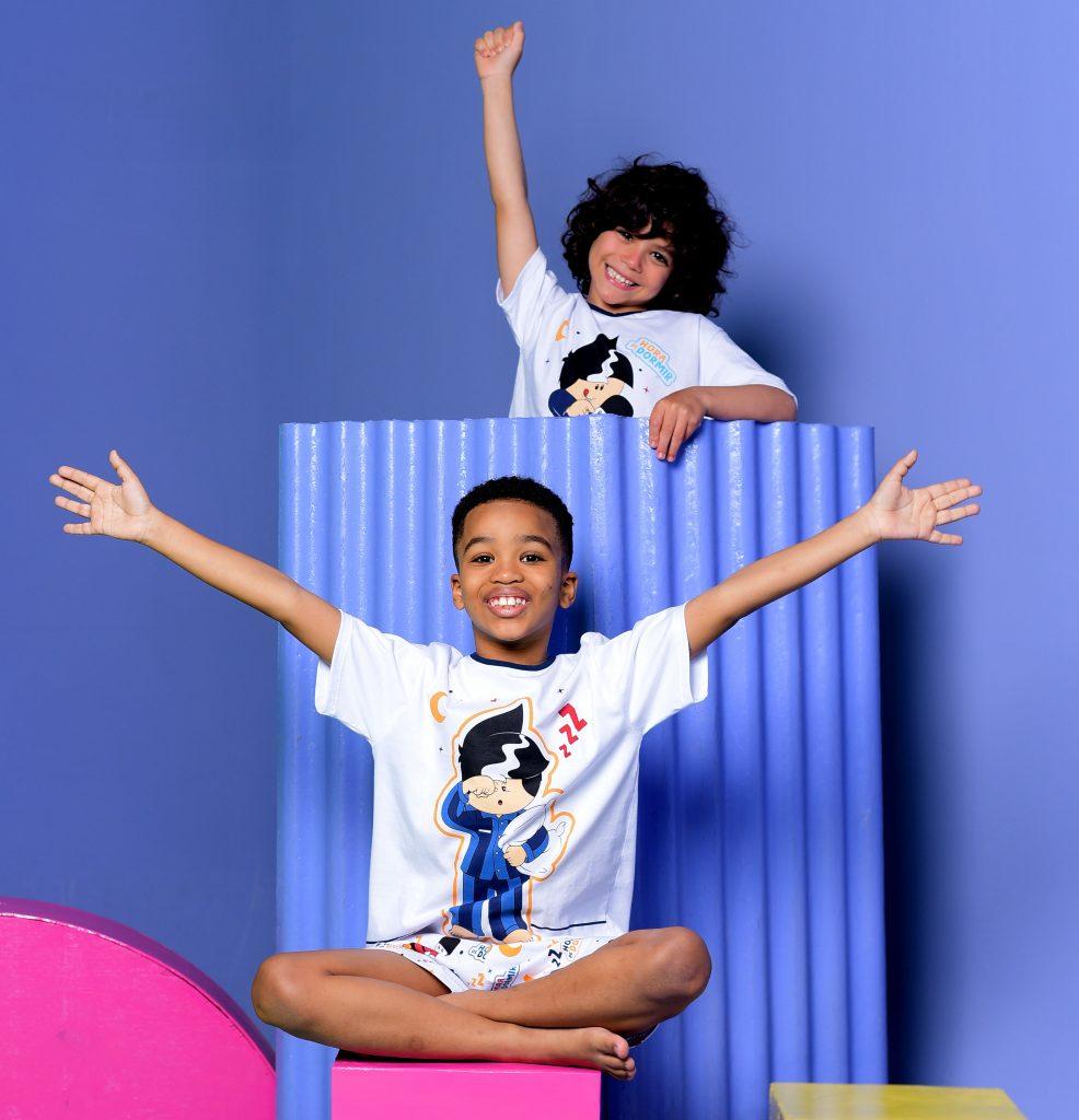 Três crianças vestindo pijamas Diamantes no fundo azul. Dois meninos e uma menina entre eles. Todos estão sorrindo e caminhando de braços dados.