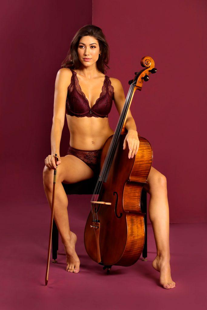 Modelo usando lingerie Diamantes na cor barolo. A modelo está sentada em um banco, tem um violoncelo apoiado na perna direta e um arco na perna esquerda.