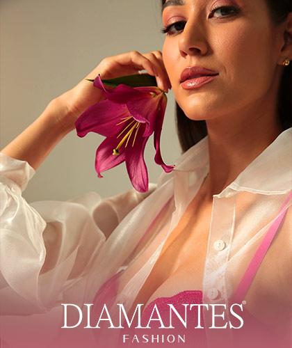Modelo vestindo sutiã lift Diamantes na cor Cerise. A modelo está usando uma blusa transparente branca e segura uma flor rosa próximo ao rosto.