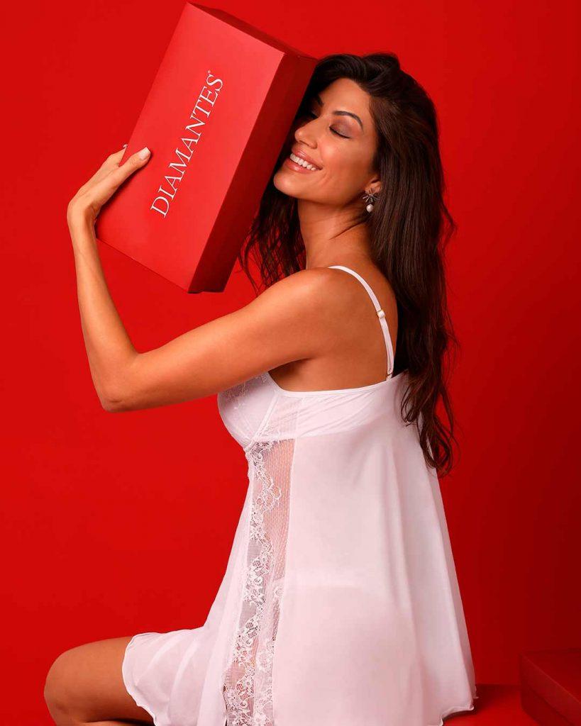 Modelo sorrindo e de olhos fechados usando camisola branco Diamantes. A modelo segura uma caixa de presente vermelha da Diamantes.