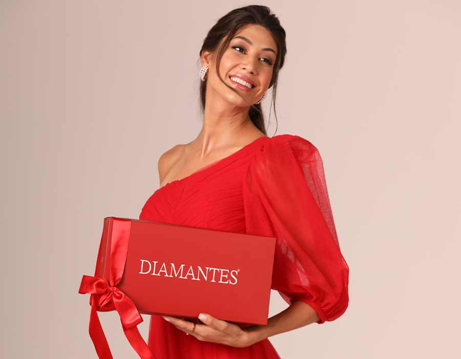 Modelo usando vestido vermelho, sorrindo e olhando para a direita. Ela segura uma caixa da Diamantes na cor vermelha e a logo na frente.