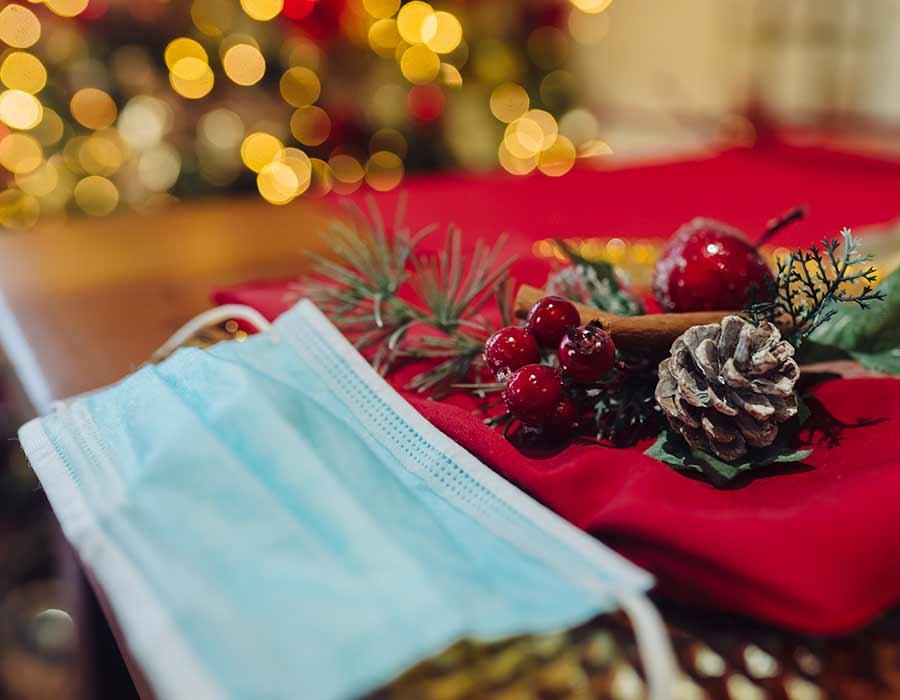 Mesa decorada de Natal com máscara de proteção perto e close-up na máscara.