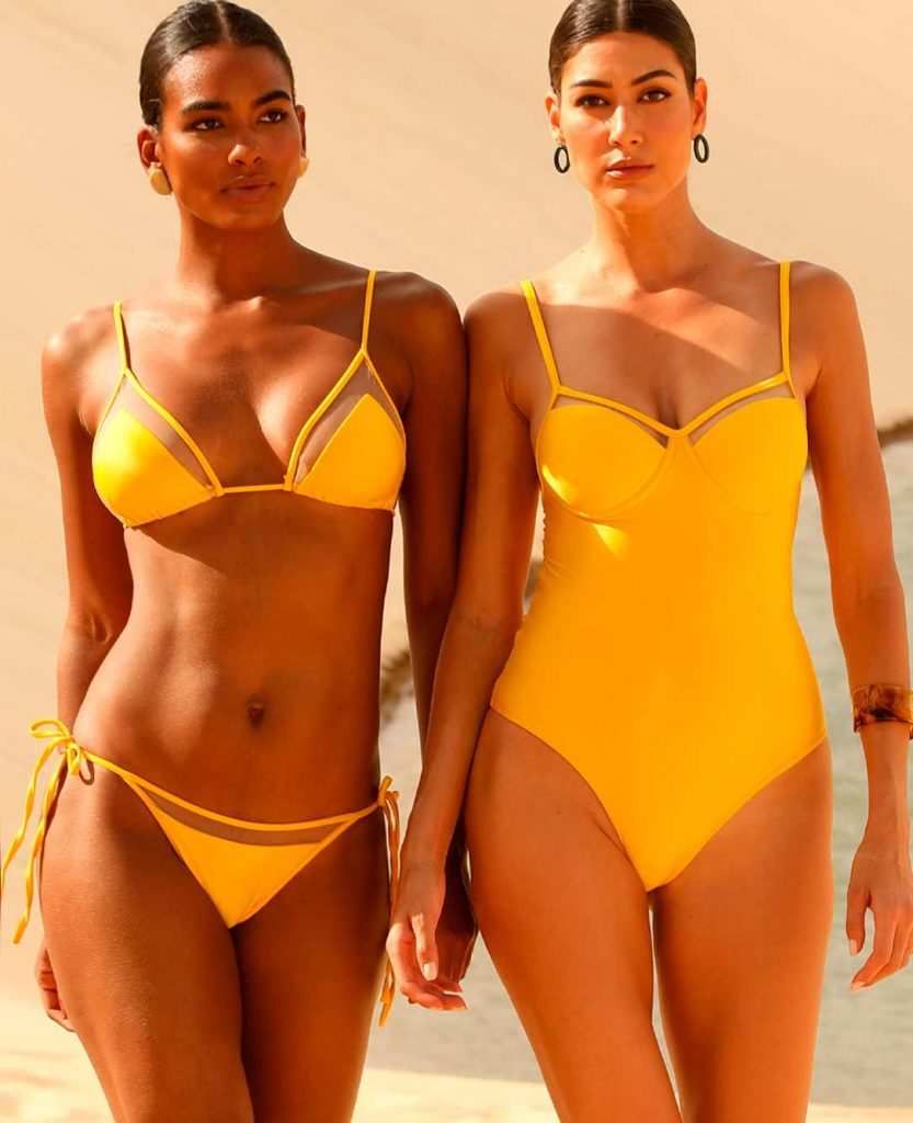Duas modelos na praia usando moda praia Diamantes. A modelo da direita está usando maiô enquanto a modelo da esquerda está usando biquíni cortininha. Ambos na cor amarela.