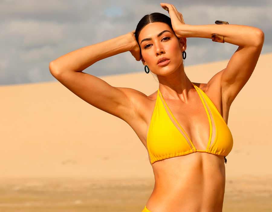 Modelo usando biquíni com sutiã top Diamantes na cor amarela.