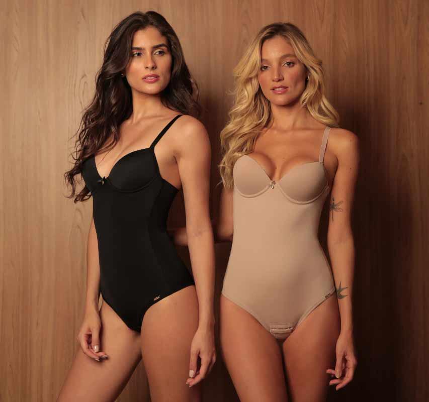 Fundo amadeirado, duas modelos usando body modelador Diamantes. Modelo da esquerda usando body modelador na cor preta e modelo da direita usando body modelador na cor chocolate.