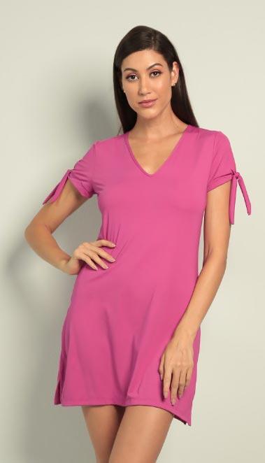Modelo veste vestido resort Diamantes na cor rosa. O vestido tem mangas curtas e amarração com lacinho.