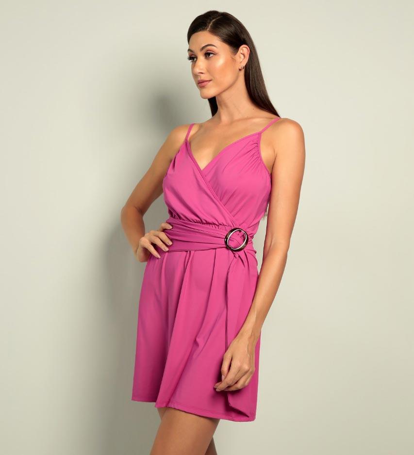 Modelo veste vestido resort Diamantes na cor rosa. O vestido tem alças reguláveis e fechamento frontal.
