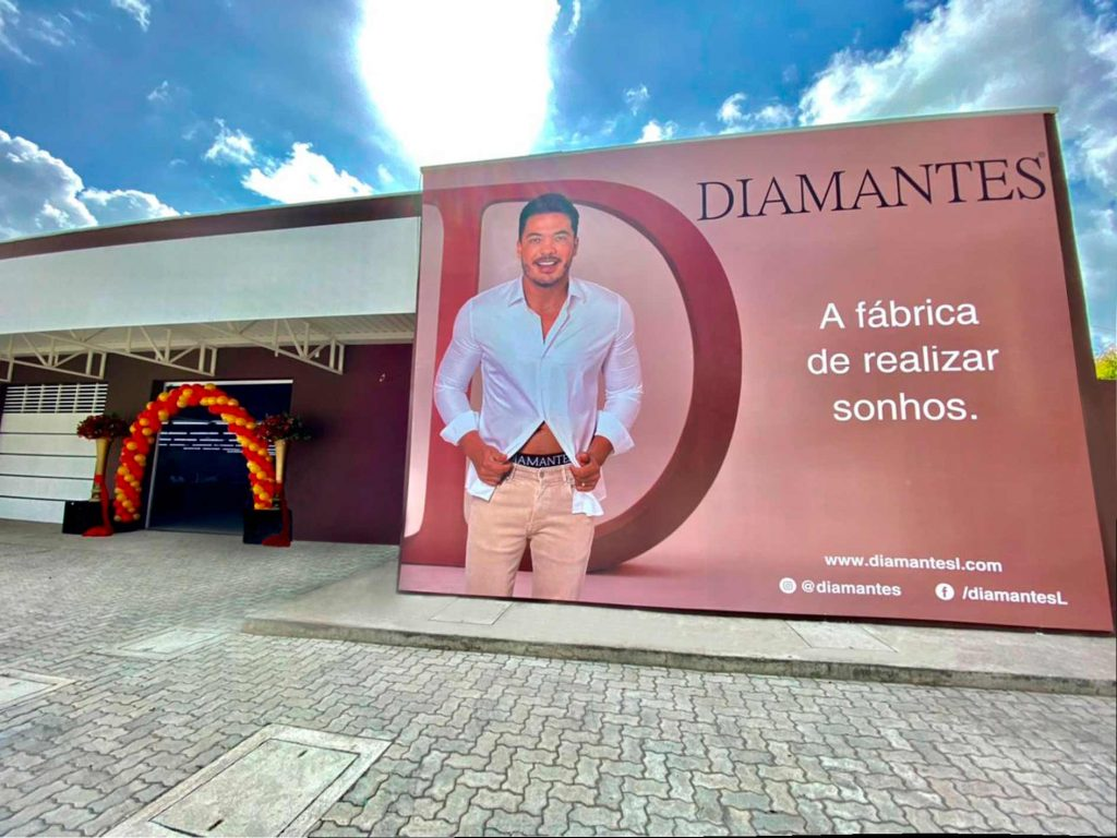 """Imagem da nova fábrica da Diamantes Lingerie, localizada em Maranguape-CE. Na entrada tem balões vermelhos e amarelos. Ao lado um banner com a imagem do embaixador Wesley Safadão mostrando o elástico da cueca Diamantes, a logo e a frase: """"A fábrica de realizar sonhos""""."""