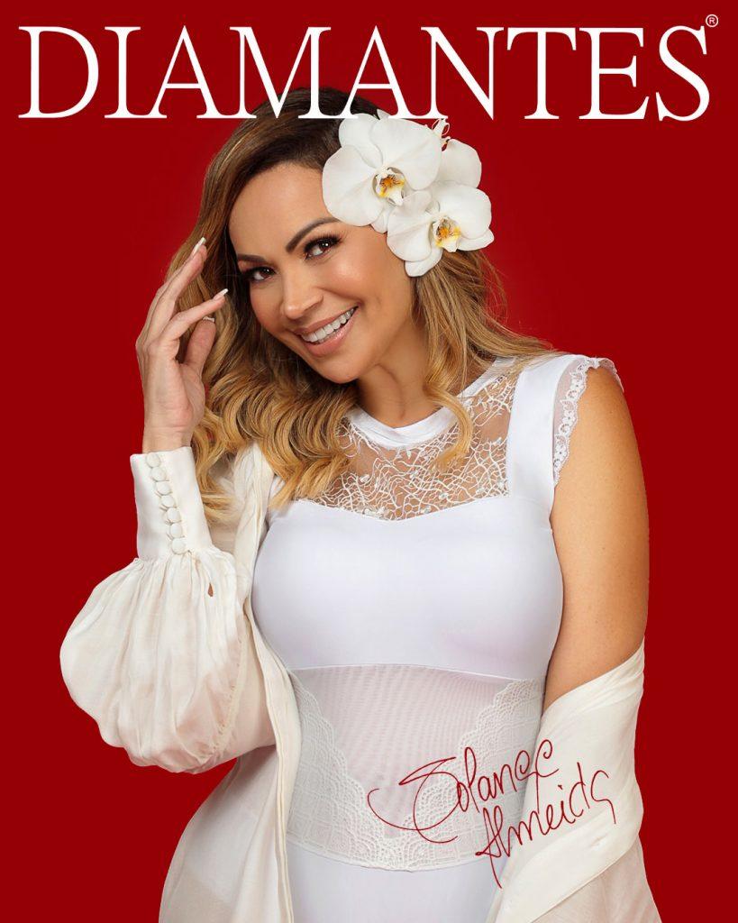 Foto com a cantora Solange Almeida usando um body Diamantes na cor branca, com uma rosa no cabelo. Acima da imagem tem a logo Diamantes e no canto inferior direito a assinatura da cantora.