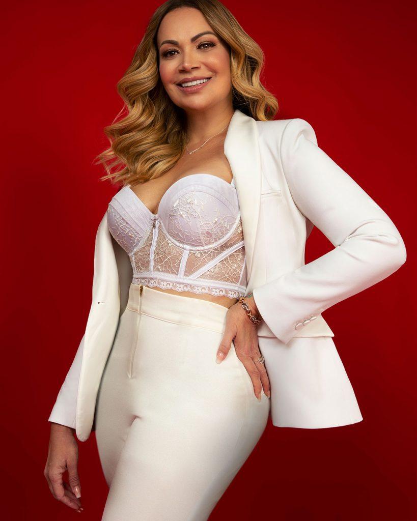 Solange Almeida veste bralette Diamantes. Usa calça e blazer para compor o look. Um look todo na cor branca. Imagem com fundo vermelho..