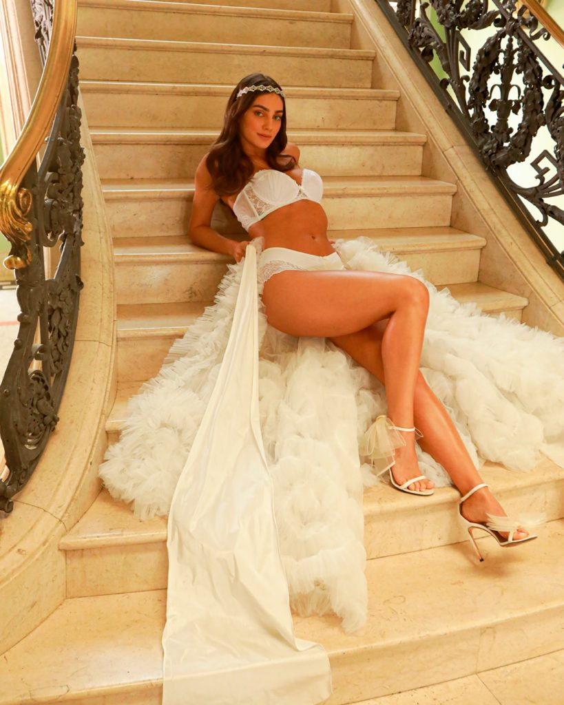 Modelo vestida de lingerie branca com saia bufante branca. Modelo está deitada em escada de mármore.