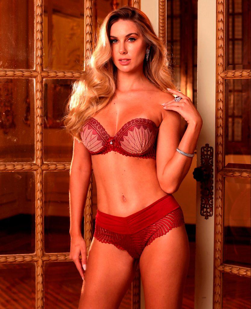 Modelo usa lingerie (sutiã com alças removíveis e caleçon fio) Diamantes na cor vermelha.
