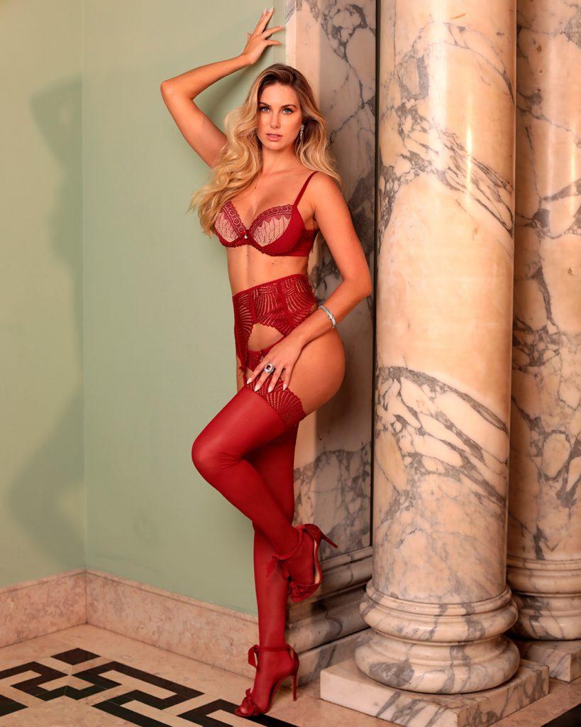 Modelo usa lingerie Diamantes na cor vermelha, composta por sutiã e calcinha, além de meia calça e cinta liga em renda exclusiva.