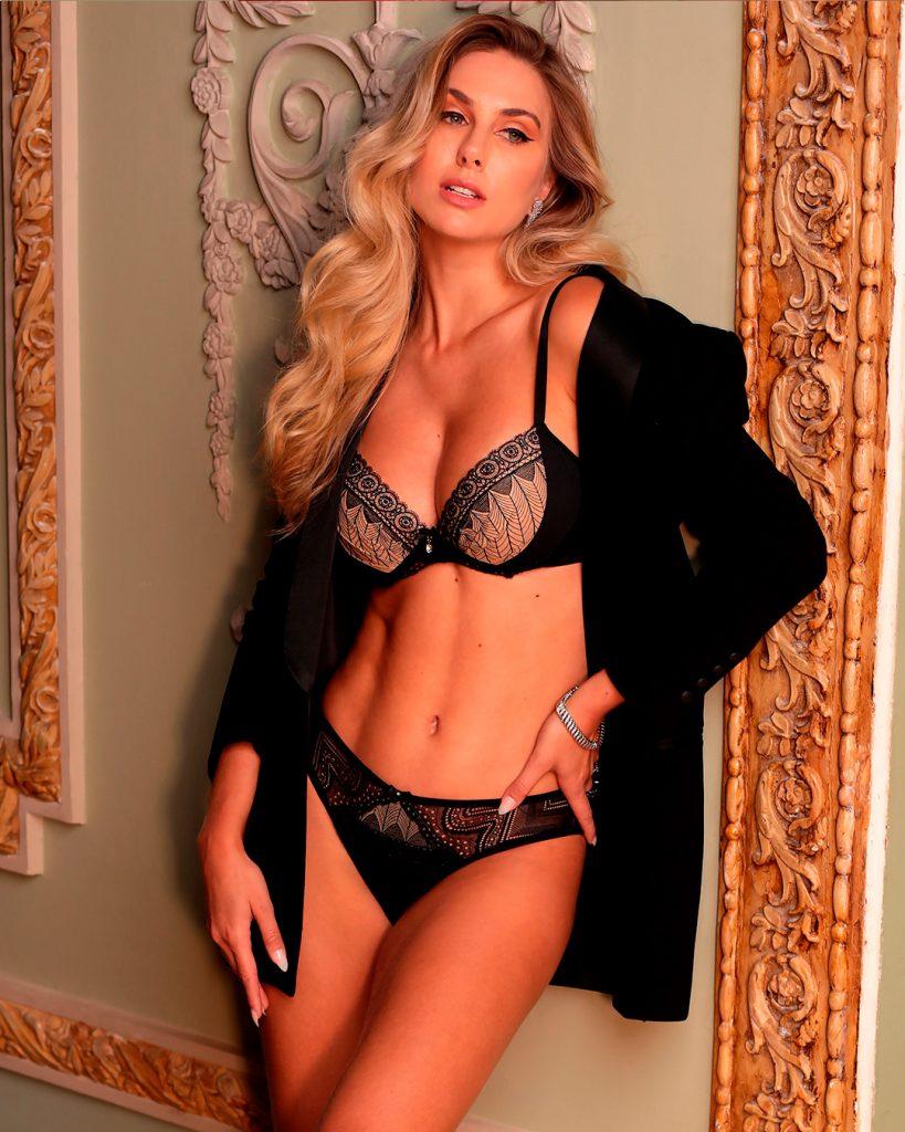 Modelo usando lingerie (sutiã lift e calcinha biquíni com renda) Diamantes na cor preta. Modelo usa sobreposição preta.