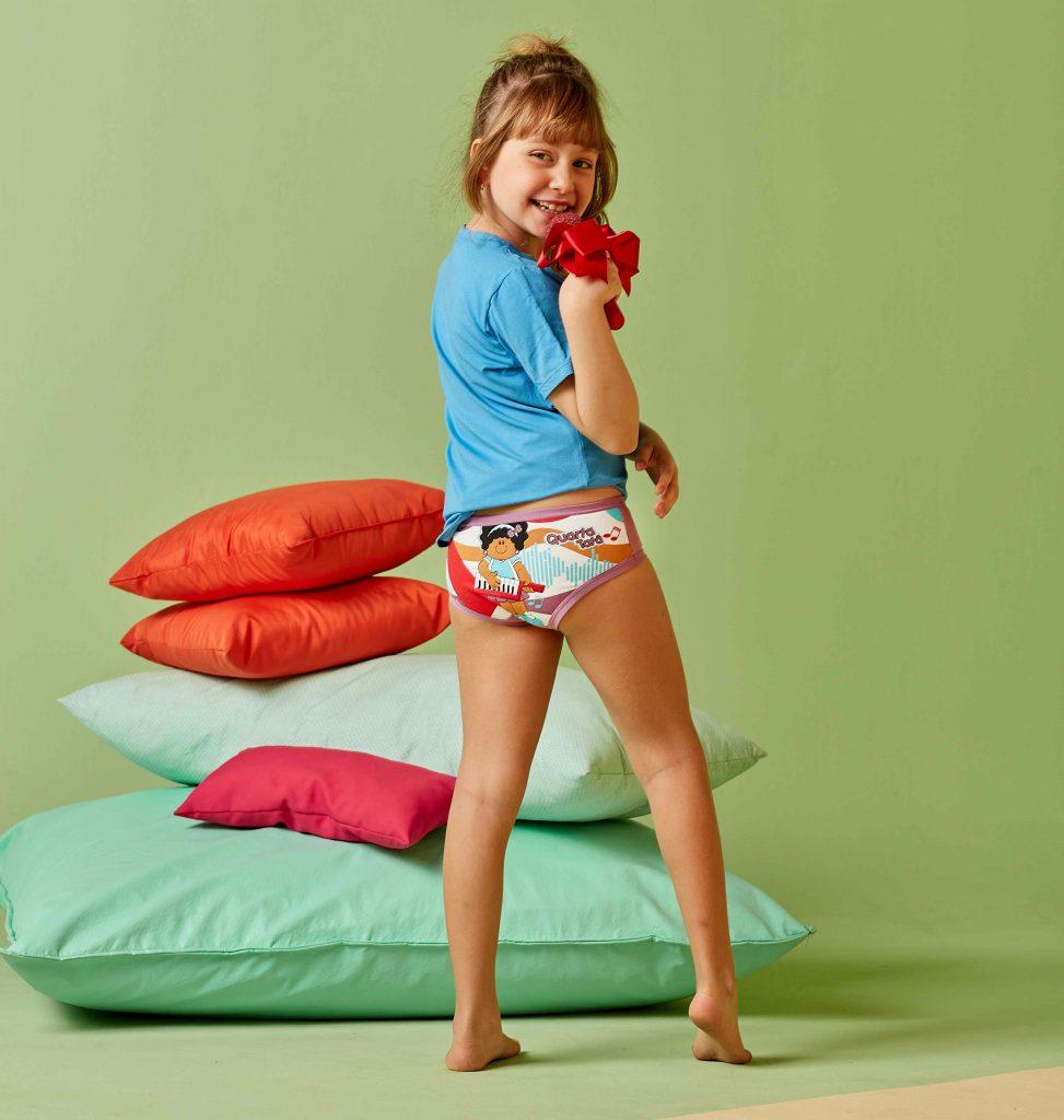 Menina usando calcinha semaninha Diamantes e uma blusa azul. A menina mostra as costas da calcinha e está cantando com um microfone.