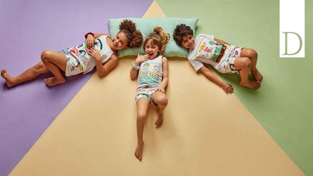 Três crianças (duas meninas e um menino) deitados no chão, olhando pra cima e usando pijamas da Diamantes Kids.